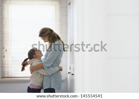 Side view of loving mother and daughter embracing by window blinds - stock photo
