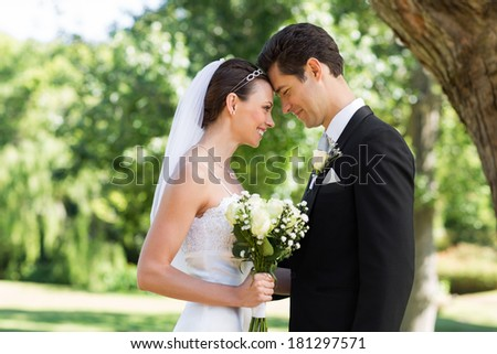 Side view of loving newly wed couple with head to head standing in garden - stock photo