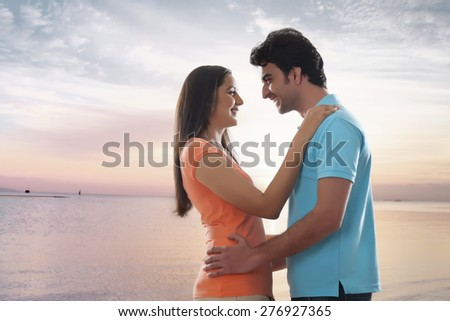 Side view of loving young couple embracing at beach - stock photo