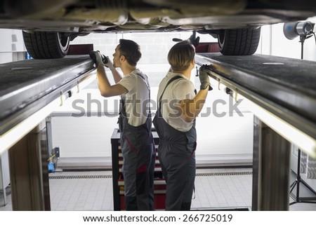 Side view of maintenance engineers examining car in repair shop - stock photo