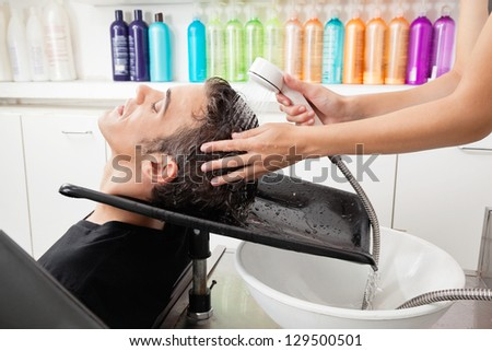 Side view of male customer having hair washed at salon - stock photo