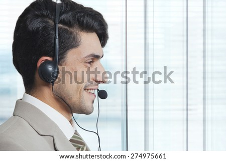 Side view of male customer service representative wearing headset in office - stock photo