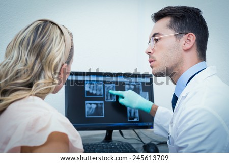 Side view of male dentist showing woman her mouth x-ray on computer - stock photo