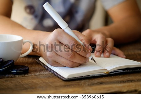 side view of male hand writing in notebook - stock photo