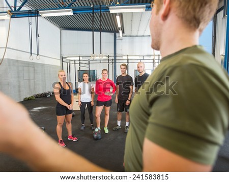 Side view of male instructor training athletes at gym - stock photo