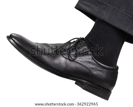 side view of male left leg in black shoe takes a step isolated on white background