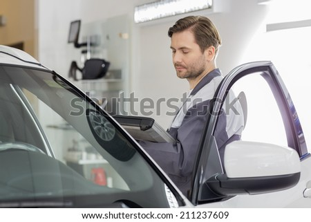 Side view of male maintenance engineer holding tablet PC while examining car in workshop - stock photo