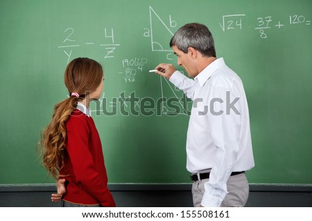 Side view of male professor teaching mathematics to female student on board in classroom - stock photo