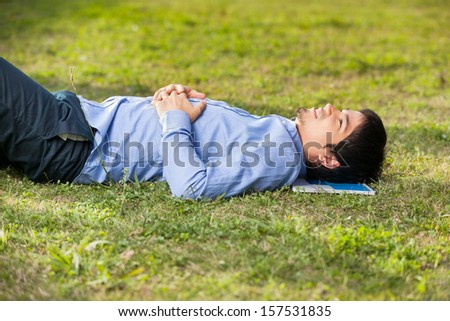 Side view of male student relaxing on grass at university campus
