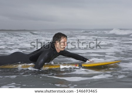 Side view of male surfer paddling on surfboard in water at beach - stock photo