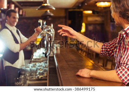 Side view of man in casual clothes ordering beer while sitting at bar counter in pub, a bartender in the background - stock photo
