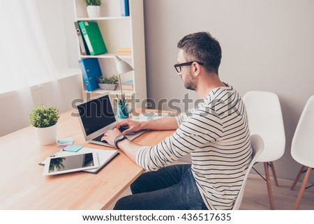 Side view of man in glasses writing book on laptop - stock photo