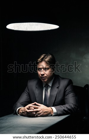Side view of man in suit sitting in dark room illuminated only by light from a lamp - stock photo
