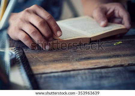 side view of man reading the bible in the darkness over wooden table.vintage effected photo. - stock photo