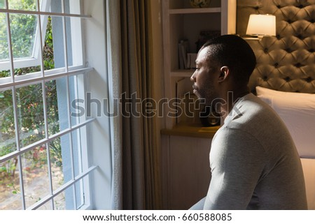 Side view of man sitting on bed by window at home