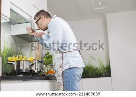 Side view of man tasting food while cooking in kitchen - stock photo