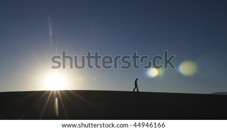 Side view of man walking in desert with sun at horizon. Horizontal shot. - stock photo