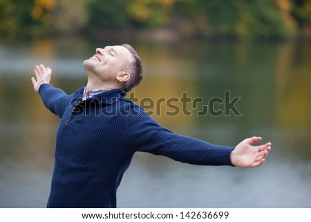 Side view of man with arms outstretched standing on pier - stock photo
