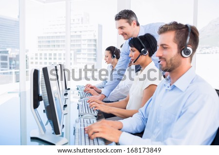 Side view of manager and executives with headsets using computers in the office - stock photo