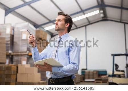 Side view of manager holding clipboard in the warehouse - stock photo