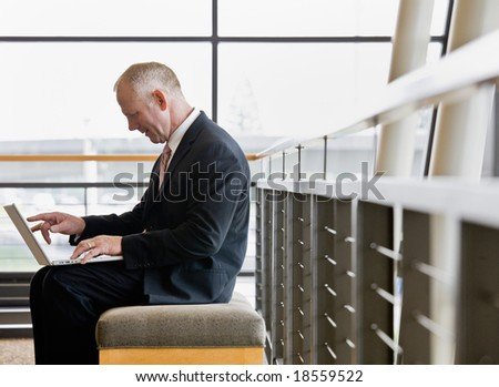 Side view of mature businessman working on laptop in office lobby - stock photo