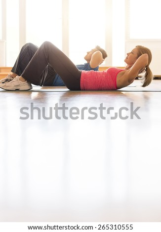 Side view of mature couple in sports clothing practicing sit-ups on hardwood floor at home - stock photo