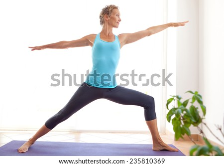 Side view of mature healthy sporty woman using a yoga mat to exercise and balance, stretching her body in a light and airy interior. Fit professional woman exercising and stretching her body, indoors. - stock photo