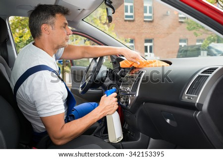 Side view of mature male worker cleaning car interior - stock photo
