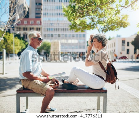 Side view of mature man sitting on bench and woman taking his photos with digital camera. Senior couple having fun on their vacation. - stock photo