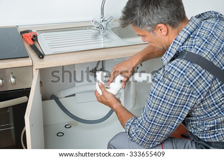 Side view of mature plumber fixing sink pipe in kitchen - stock photo