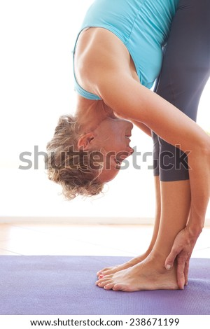 Side view of mature professional woman exercising and stretching her body doing flexibility exercises and bending her back over, standing in a yoga mat indoors. Senior woman fit and healthy lifestyle. - stock photo