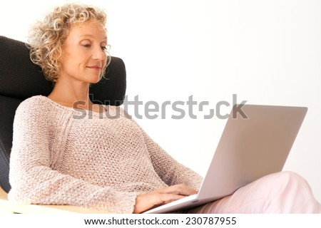 Side view of mature successful professional woman sitting and relaxing in an armchair at the office using a laptop computer and working, interior. Technology at work and lifestyle at home.