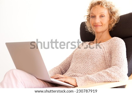 Side view of mature successful professional woman sitting and smiling in an armchair at the office using a laptop computer and working, interior. Technology at work and lifestyle at home. - stock photo