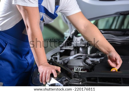 Side view of mechanic checking motor oil in a car with open hood - stock photo