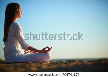 Side view of meditating woman sitting in pose of lotus against blue sky outdoors - stock photo