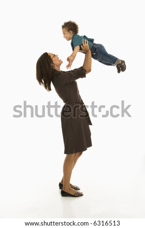 Side view of mid adult African American mom lifting happy toddler son into air above head. - stock photo