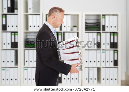 Side view of mid adult businessman carrying binders in office - stock photo