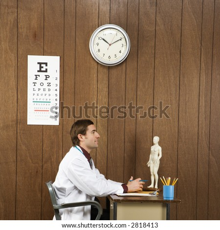 Side view of mid-adult Caucasian male doctor sitting at desk.
