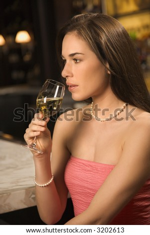 Side view of mid adult Caucasian woman sitting  at bar drinking glass of white wine. - stock photo