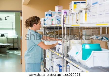 Side view of mid adult female nurse working in storage room of cancer hospital - stock photo