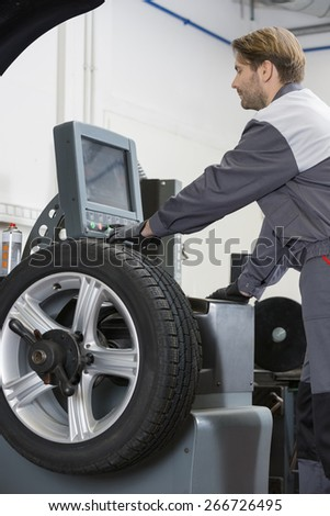 Side view of mid adult male mechanic repairing car's wheel in workshop - stock photo