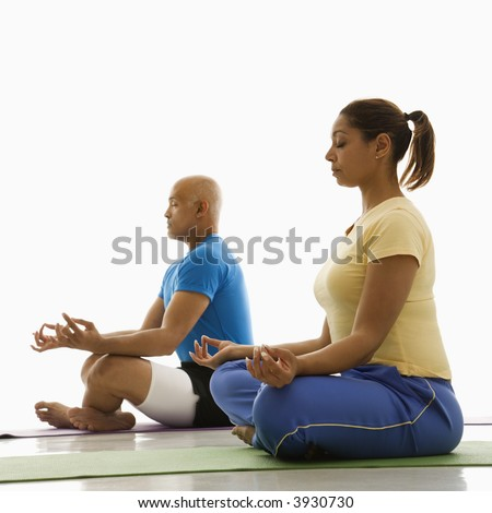 Side view of mid adult mult-iethnic man and woman sitting in lotus position on exercise mats with eyes closed and legs crossed.