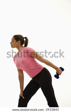 Side view of mid adult multi-ethnic woman wearing pink shirt exercising with dumbbell.