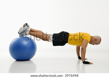 Side view of mid adult multiethnic man doing pushups while balancing on blue exercise ball. - stock photo