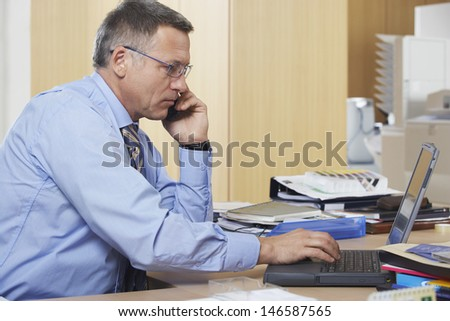 Side view of middle aged businessman on call while using laptop at desk - stock photo