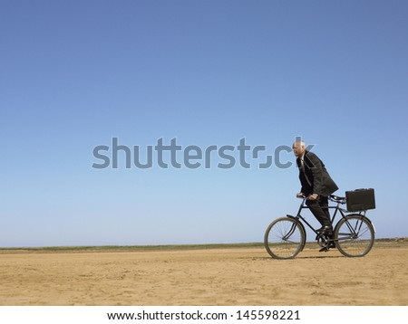 Side view of middle aged businessman with briefcase riding bicycle in desert