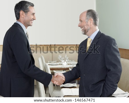 Side view of middle aged businessmen shaking hands in restaurant - stock photo