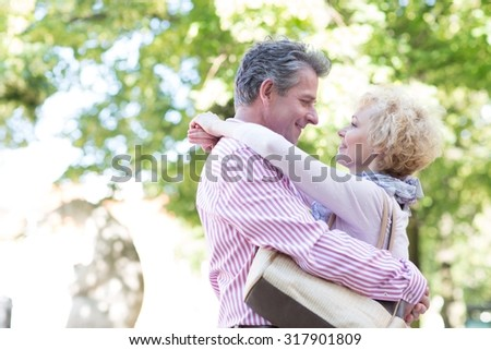 Side view of middle-aged couple embracing while looking at each other in park - stock photo