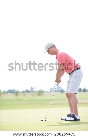 Side view of middle-aged man playing golf at course - stock photo