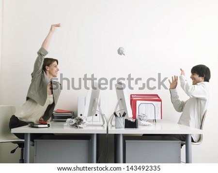 Side view of mischievous businesswoman throwing paper ball on male executive over desks - stock photo